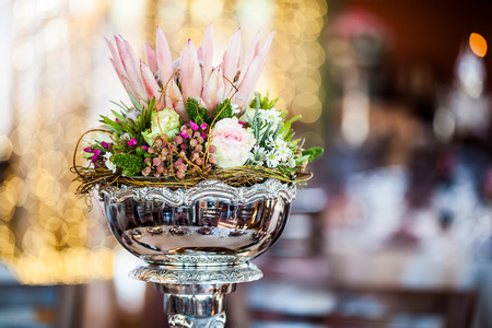 cropped image of a silver centerpiece filled with wild flowers and roses and a king protea in the middle Stock Photo