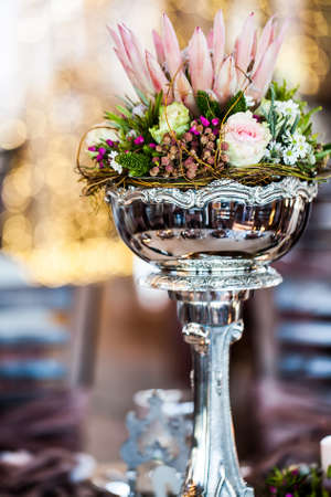 image of a detailed silver centerpiece arranged with wild flower, roses and a king protea in the middle