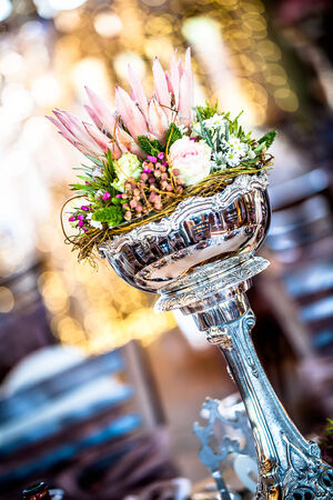 a silver centerpiece at an angle filled with wild flowers, roses and a king protea in the middle
