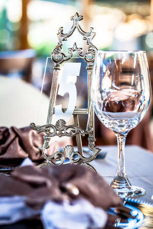 a close-up image of a detailed silver and glass table number stand with a wine glass in front of it on the table