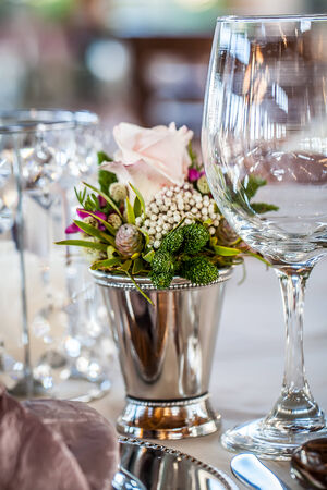 a close-up image of a small silver vase filled with fresh wild flowers surrounded by crystal glasses Standard-Bild