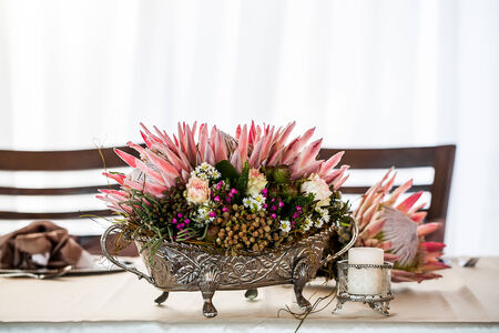 a detailed silver centerpiece filled with wild flowers and three vibrant proteas placed on a decorated table with candle holders