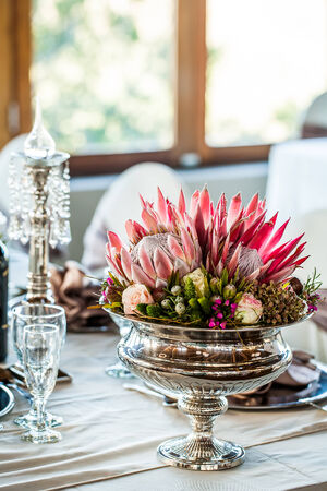 image of a silver vase filled with wild flowers and king proteas  on a decorated table
