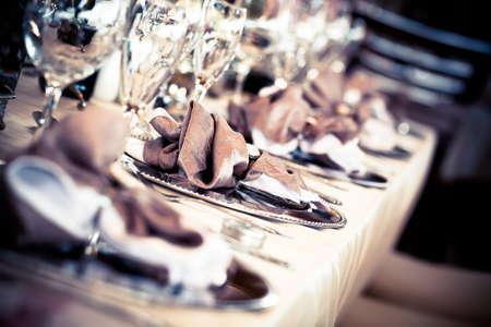 image of a row of silver plate settings with decorated napkins placed on top and crytal glassed in front of the settings