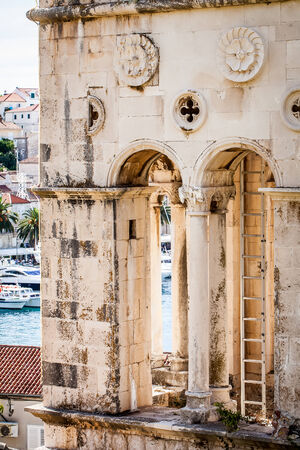 a cropped image of the part of an old historic church tower and the harbour peeking out in the background Stock Photo
