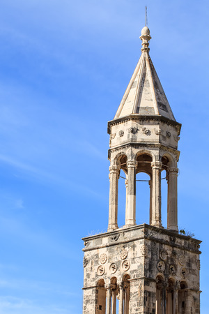 the top of an old stone church tower with the bright blue sky in the background