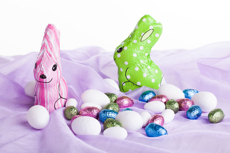 image of chocolate bunnies in colorful wrapping with different sized and colored chocolate eggs all placed on purple organza material Stock Photo