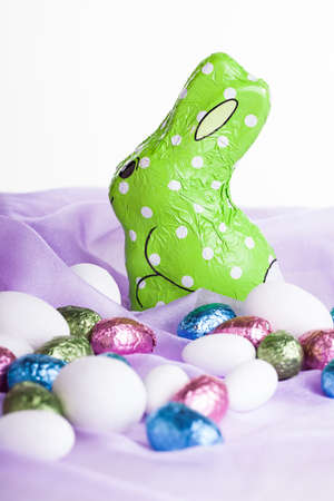 a green wrapped chocolate bunny placed on light purple organza material with various chocolate colored egss surrounding it Stock Photo