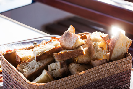 freshly cut homemade bread in a basktet on a table with the sun shining on it