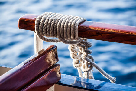 a close-up image of rope knotted to the hangle bar on the boat with the blue waters in the background Stock Photo