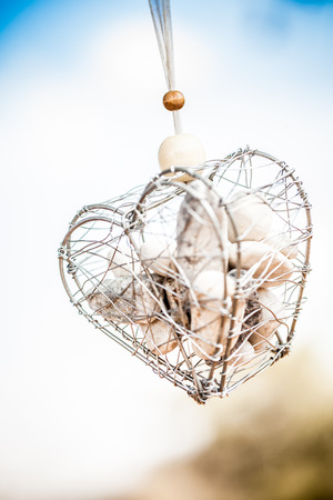 a swinging wire heart filled with small various rocks in the bright outdoors