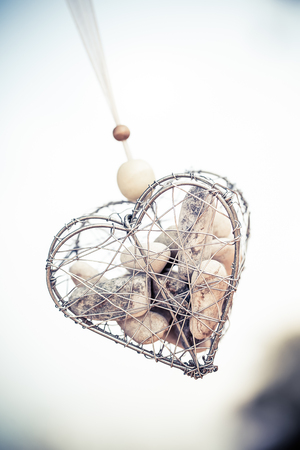 a wire heart hanging from some ribbon filled with various small rocks Standard-Bild