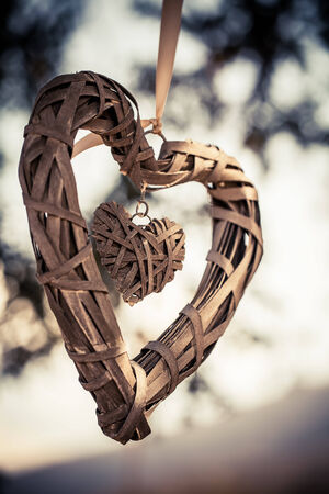 a close-up of a woven wood heart with a smaller heart inside hanging by a ribbon in the outdoors