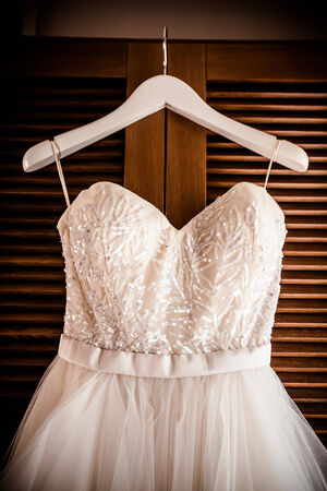 image of the bodice of a weeding dress on a hanger  against a wooder relolving door