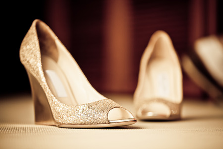 wedges: a pair of textured golden shoes on the carpeted floor Stock Photo