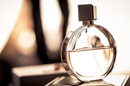 a round bottle of womans frangrance resting on a box in light shining in from a window