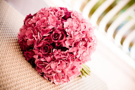 a bridal bouquet of pink hydrangeas and roses placet on a woven surface