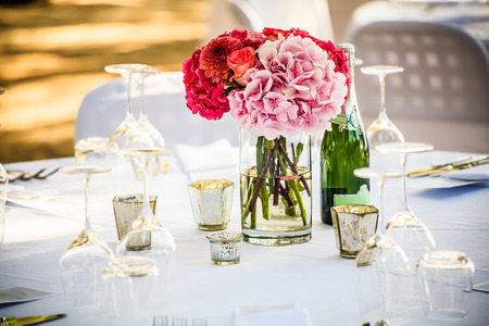 shades of pink hydrangea centerpiece placed on a crisp white decorated table Stock Photo