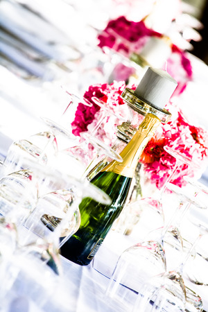 a bottle of champange and a candle with flowers placed in the center of the white decorated table amoung crystal glasses