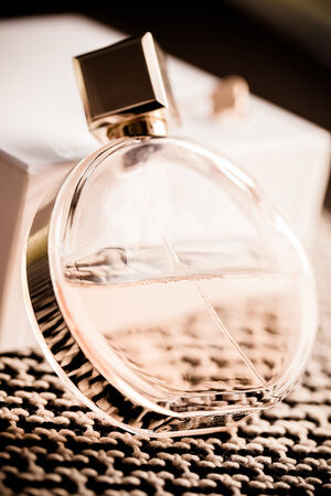 a round bottle of womans fragrance laying at an angle agains a white box and textured carpet
