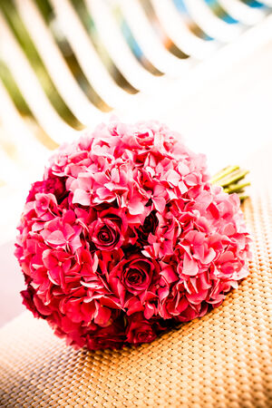 a vibrant pink hydrangea an rose bouquet resting on a woven surface
