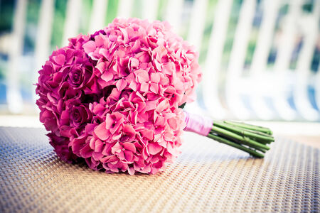 a sorft pink hydrangea an rose bridal bouquet resting on a wovan surface Standard-Bild