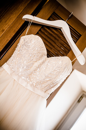 an angled image of the bodice of a wedding dress on a hanger hanging from a revolving wooden door Stock Photo