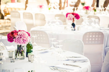 a white crisp decorated table with a pink hydrangea centerpiece and multiple other decorated tables in the background Stock Photo