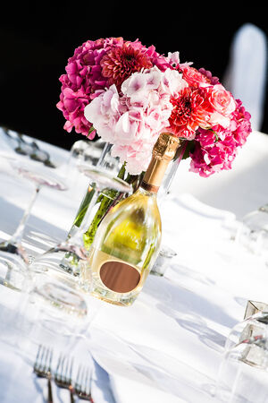 an angles image of a pink hydrangea centerpiece and a bottle of champagne on a decorated white table