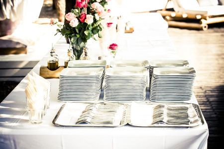 an image of multiple white plates and cutlery stacked on a white decorated table