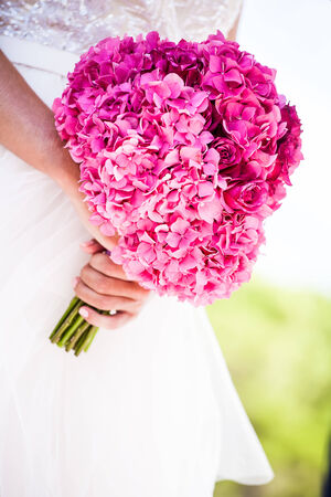 a close-uup image of a caucasian brides hands holding her pink hydrangea and rose bouquet
