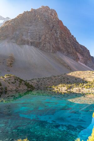 The beautiful mountain trekking road with clear blue sky and rocky hills and the view of Alaudin lake in Fann mountains in Tajikistan
