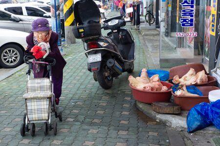 Wando/South Korea-04.11.2016:The grandwoomen and pigs heads infrant the butcher shop Stok Fotoğraf