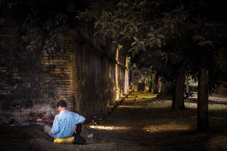 The malaysian man playing the guitar in the park Archivio Fotografico
