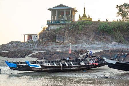 Duya/Myanmar-24.02.2017:The boat with fisherman in small fisherman village in Myanmar and the buddhist temples