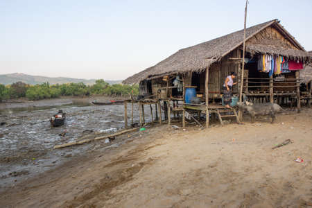 Duya/Myanmar-24.02.2017:The bamboo house, woman and her pig