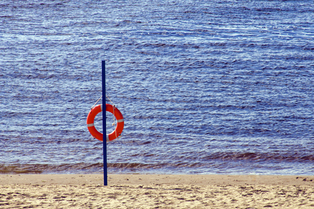 Red lifebuoy on sandy beach in hot summer evening. Stock Photo