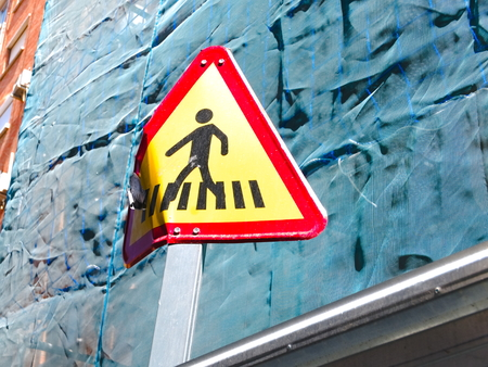 Malaga/Spain - 03-22-2019 : Bent yellow and red triangular road sign indicating the presence of a pedestrian crosswalk.