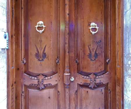 Nice view of an old antique wooden entrance door of an old European typical building. Metallic golden shiny knockers. Stock Photo