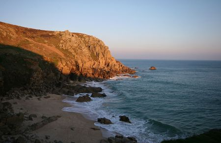 over packed: The evening sun gives a golden colour to the headland at Porthchapel at the same time casting a shadow over the beach after a day packed with people. Stock Photo