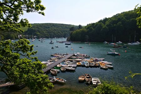 pink cruiser: This mooring area on the river Yealm in the South Hams Devon is multifunctional, it serves the local community as a ferry stage and somewhere to moor their boats plus it is a landing stage for visiting boats, the area is surrounded by woods, the villages