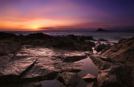 aura sun: The sun setting over Mounts Bay in West Cornwall as waves crash around St Michaels Mount and the foreshore of Trenow beach, the stormy conditions create an aura of colours. Stock Photo