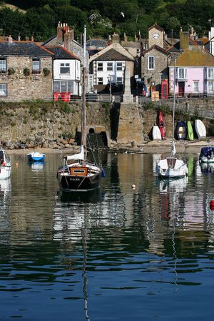 mousehole: This yacht moored in Mousehole harbour formed an almost mirror like reflection in the morning sun Stock Photo