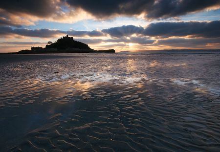 The pools trapped by the sand ripples on the beach reflect the sunset over Mounts Bay West Cornwall, UK photo