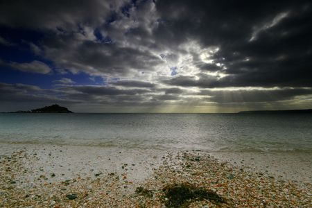 The evening light streams through a storm cloud over Mounts bay West Cornwall photo