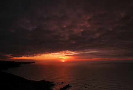 a spectacular sunset over the sea as seen from Crackington Haven Cornwall UK photo