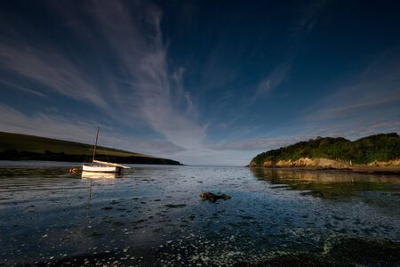 A small yacht floats gently on the early morning tide in the Erme estuary, South Hams, Devon, UK photo