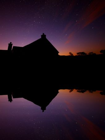 aura sun: An old watermill next to a lake, taken on a long exposure just before daybreak. Star trails and clouds show movment whilst the aura created by the rising sun can be seen.