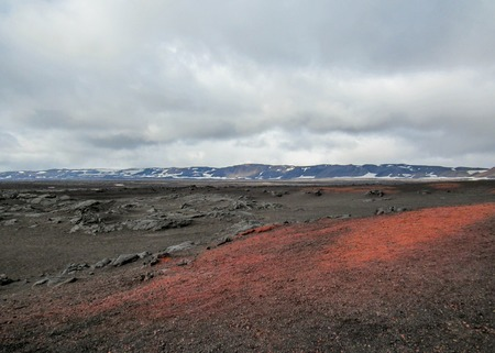 Volcanic landscape with red and black barren ground and mountains on the background, summer in Askja, remote part of the central highlands of Iceland, Vatnajokull National Park, Europe