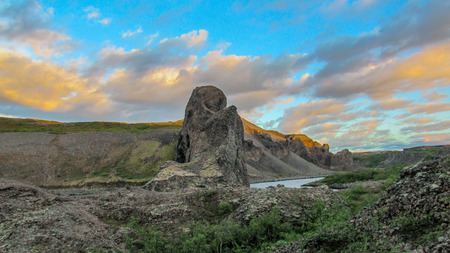 Sunset panorama of unique columnar rock formations, radial arrangement at the entrance to Vesturdalur, Asbyrgi, with dramatic sky at Vatnajokull National Park, Northern Iceland, Europe